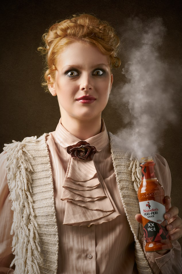 Woman is holding a bottle of spicy sauce with smoke coming out of the open bottle