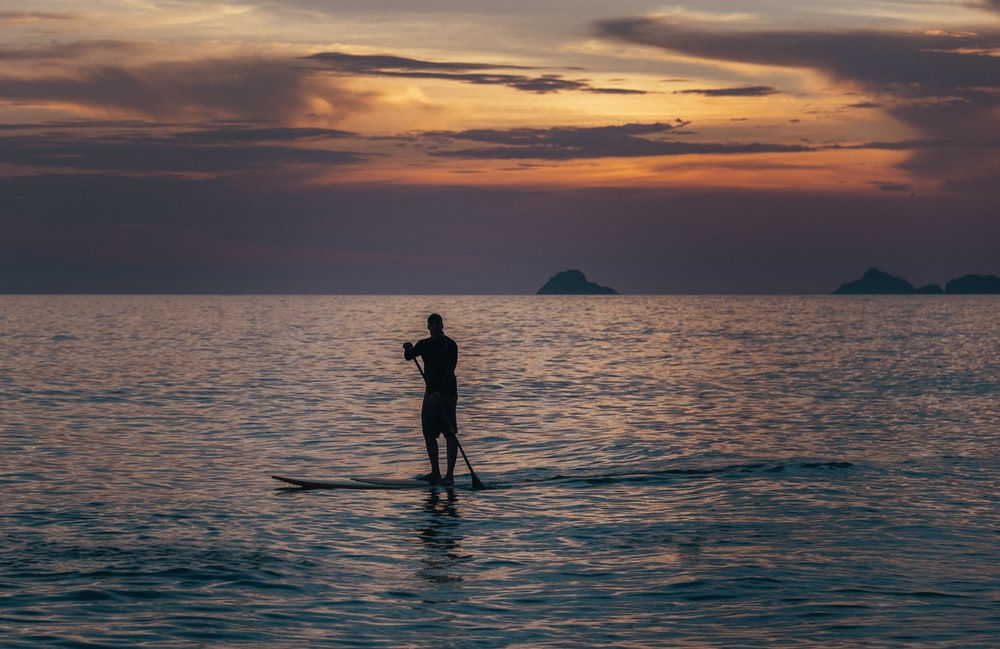 man standing on board paddling at see during sunset