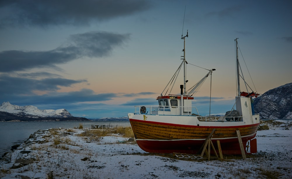 red and white wooden boat near seashore
