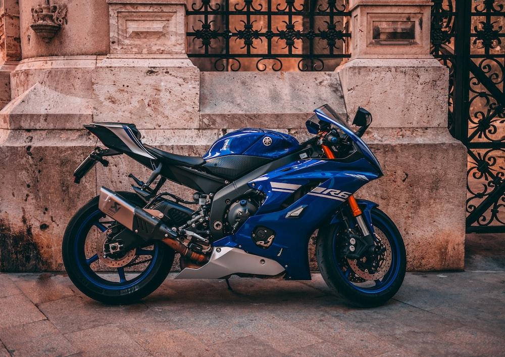 parked blue sports bike near black metal gate