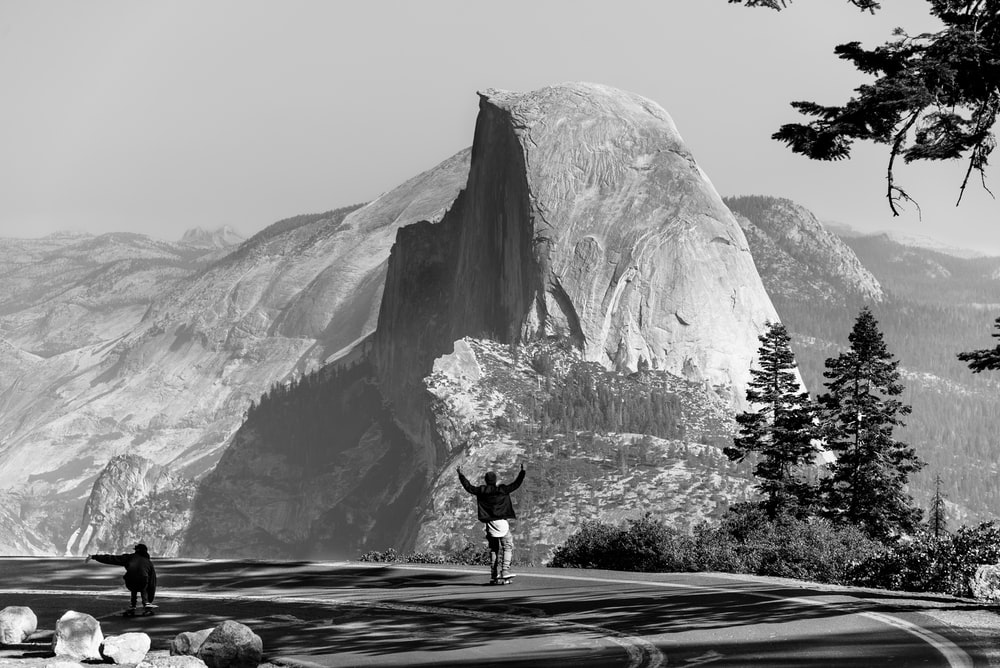 grayscale photo of man standing on asphalt road fornt of mountain