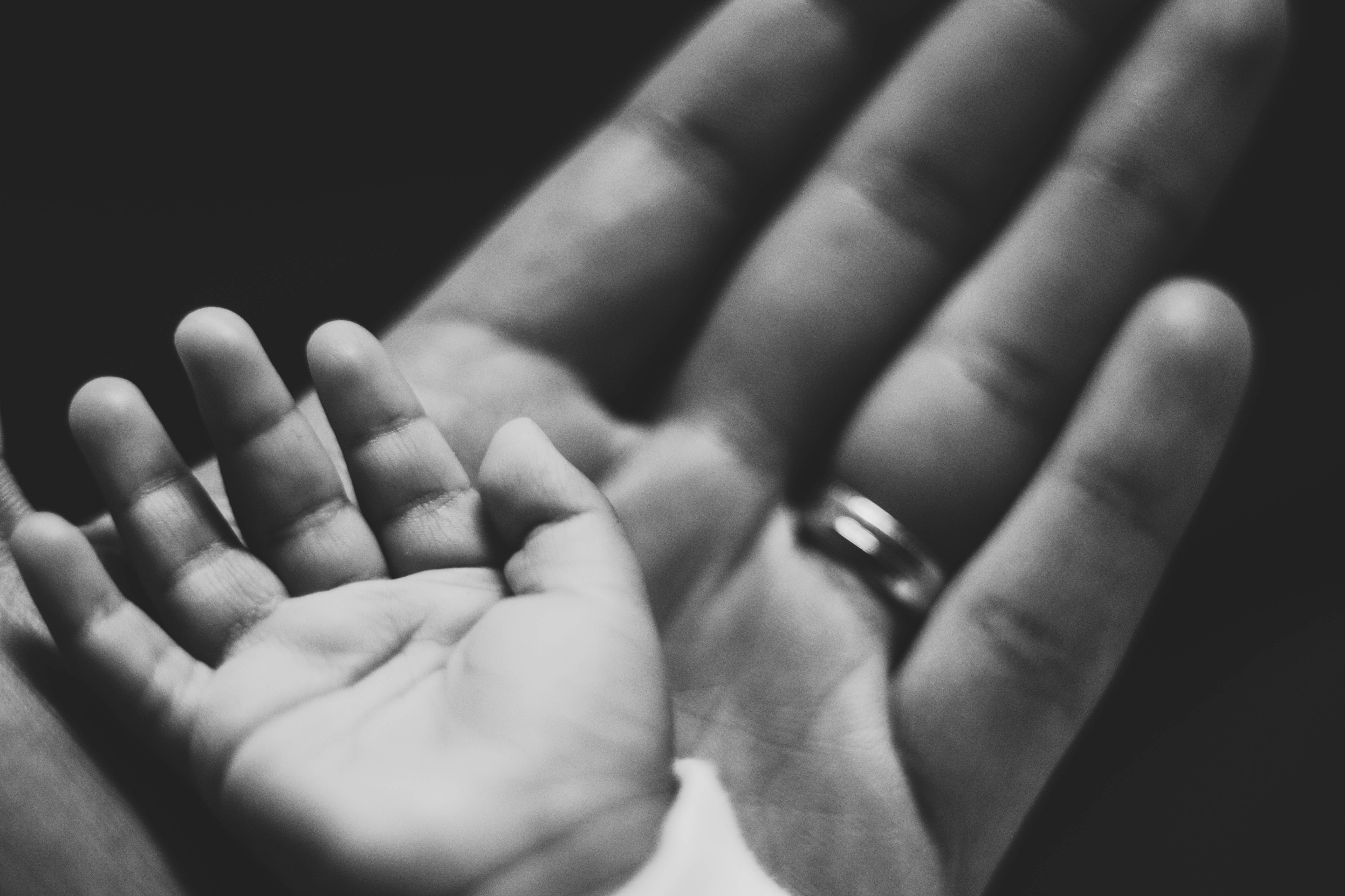 grayscale photography of baby's palm on adult