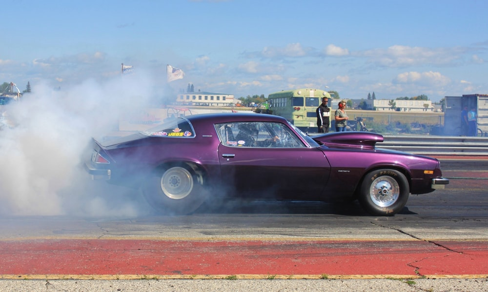 purple coupe burning out on road during daytime