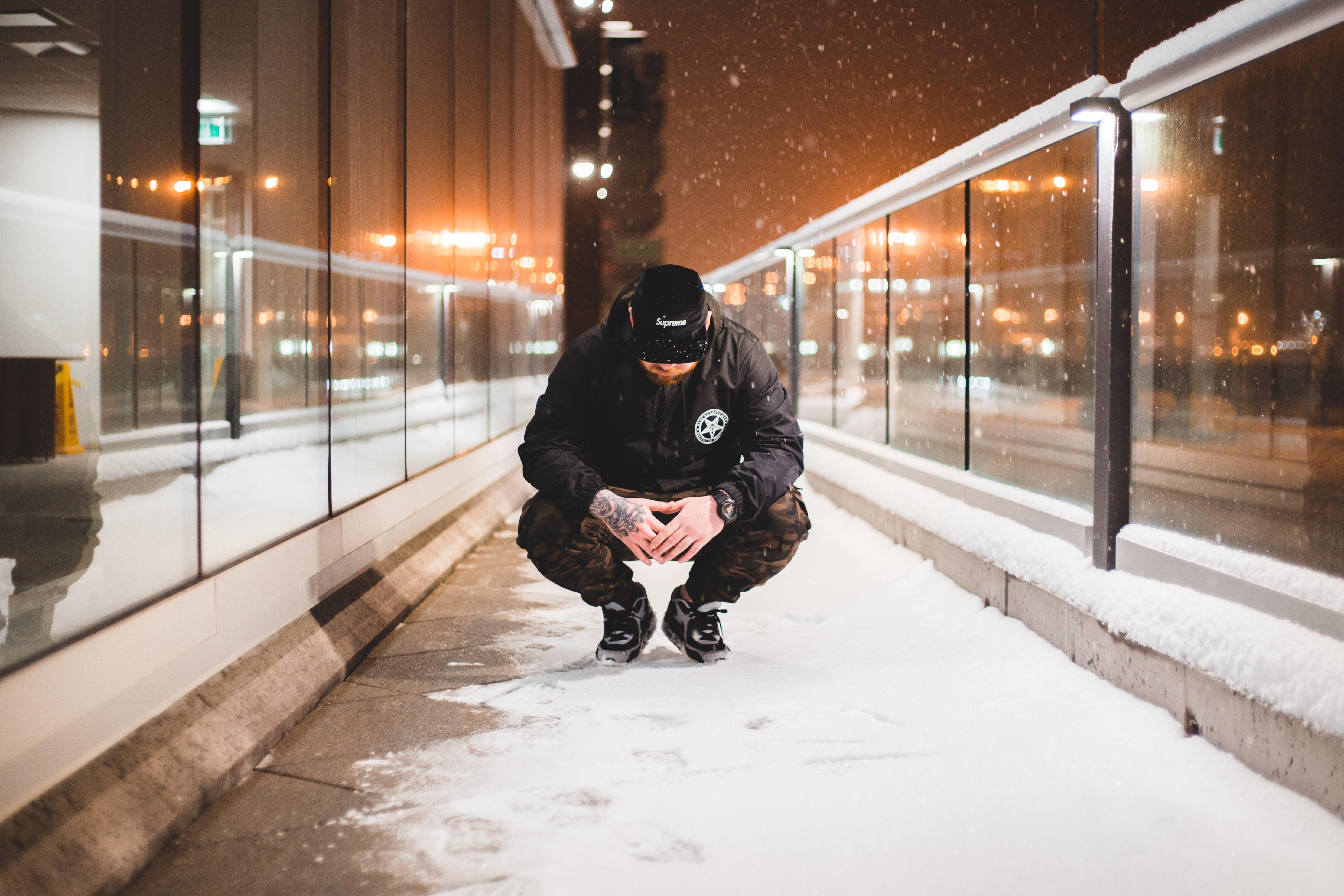 man squat on pavement