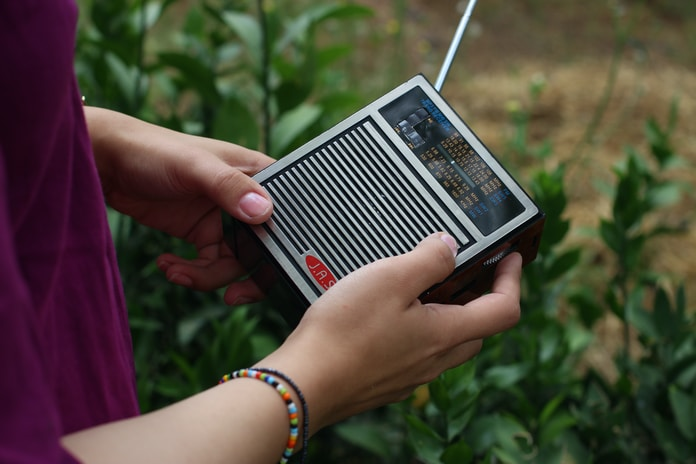 person holding black and gray radio