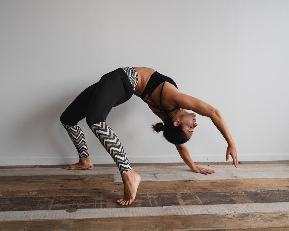 woman bending backwards beside wall