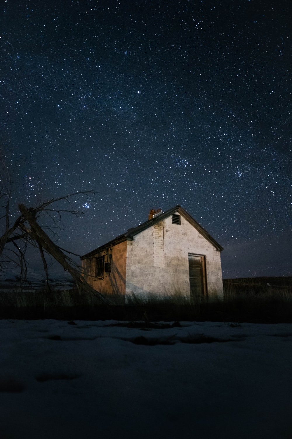 house under clear sky full of stars at night