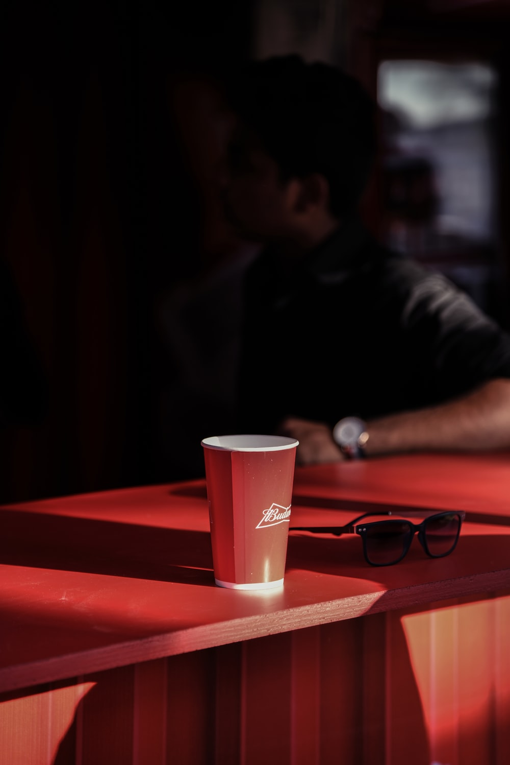 man sitting beside red and white cup next to black framed sunglasses