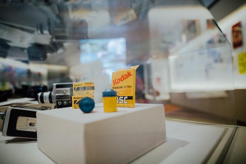 yellow and blue Kodak camera film container