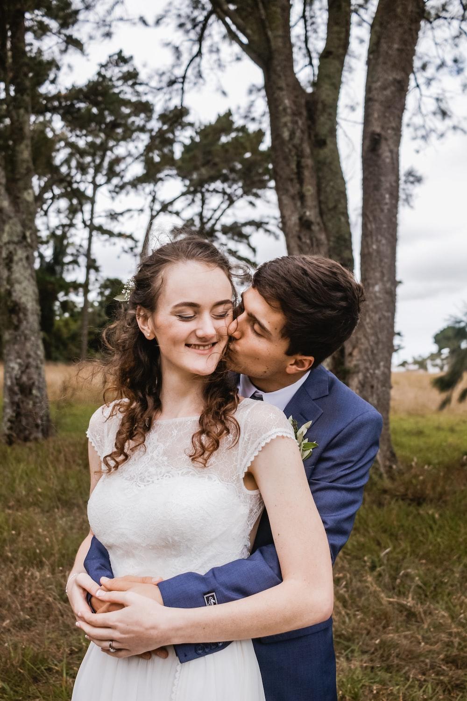 man kissing woman under tree