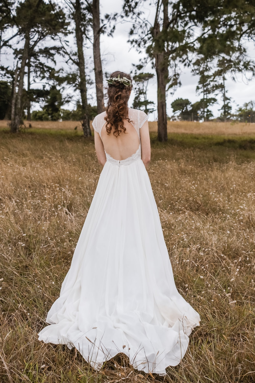 woman wearing backless wedding gown standing in the middle of brown grass field