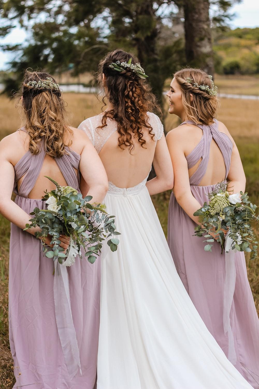 three women hiding flower bouquets