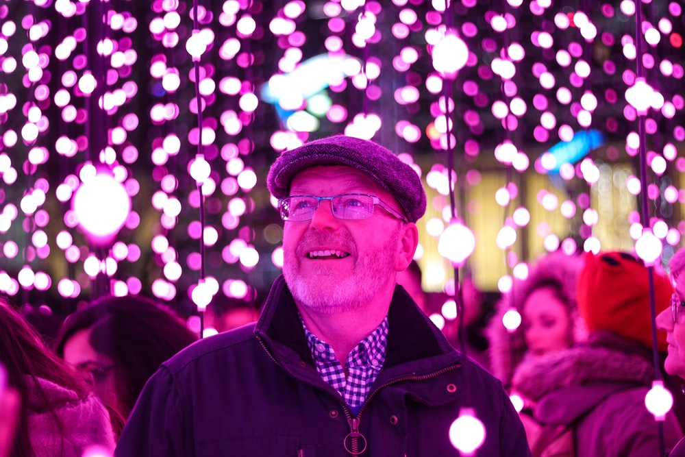 man in black jacket looking at the purple string lights