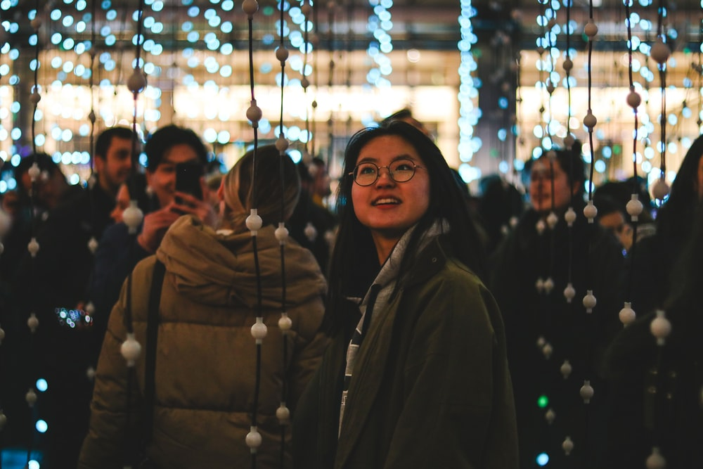 woman wearing gray jacket surrounded by string lights