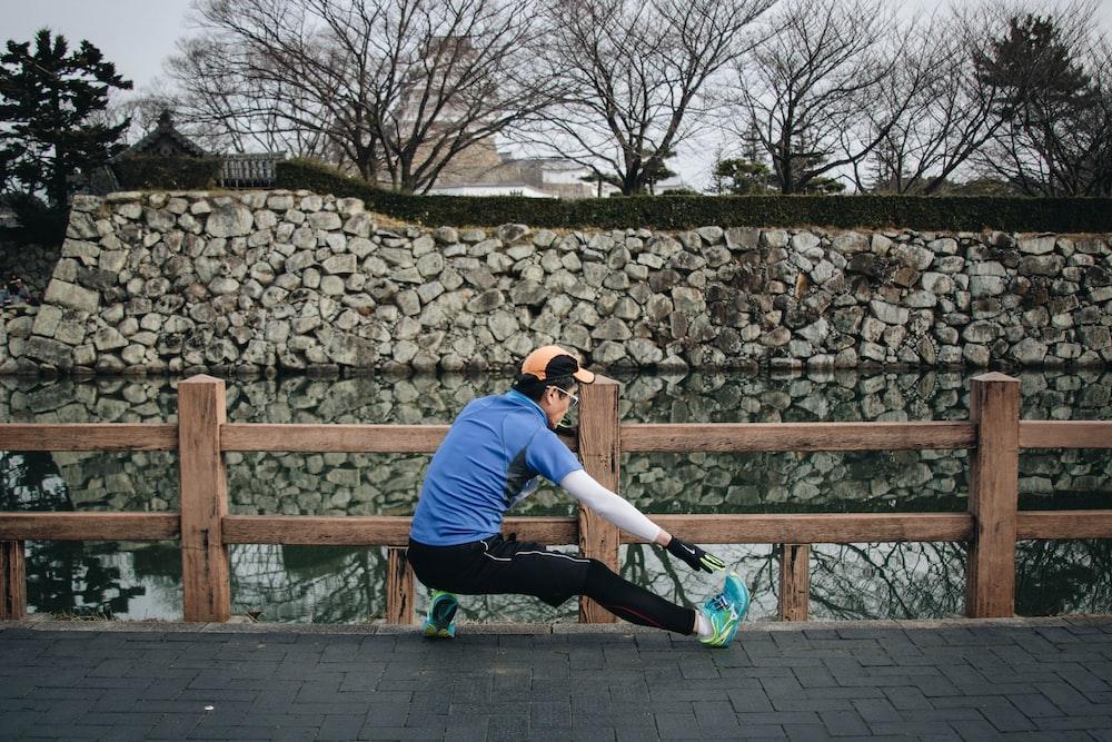 man sitting near fence during daytime