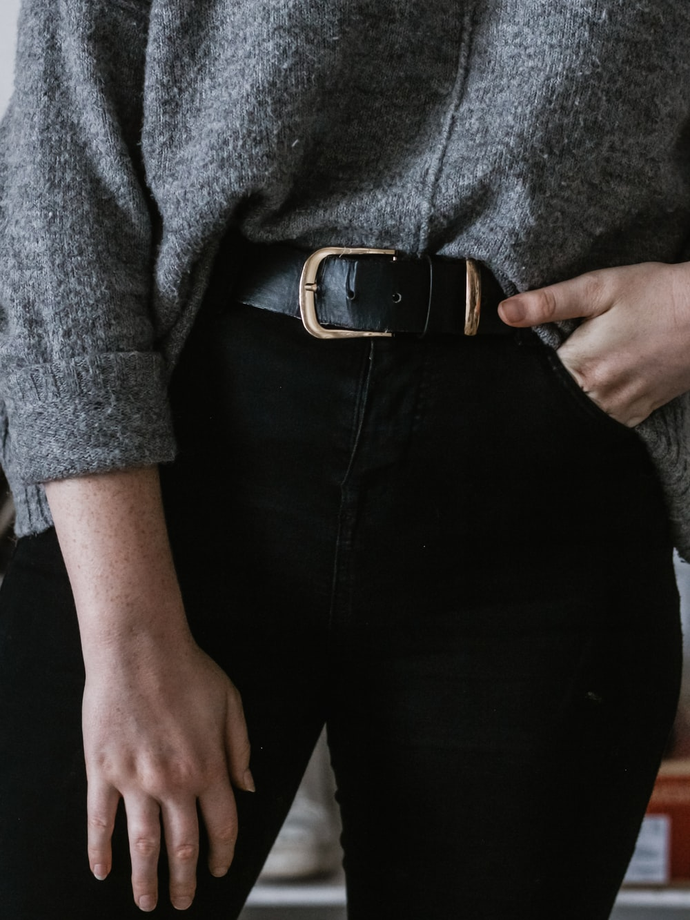 person wearing black leather belt