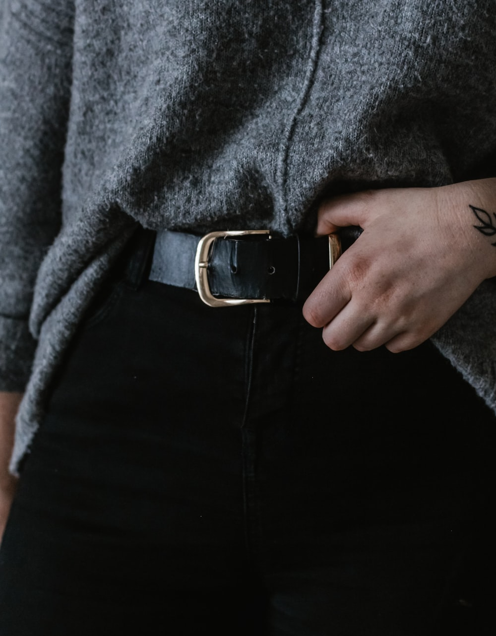 person wearing black and silver belt with buckle, black bottoms, and gray top