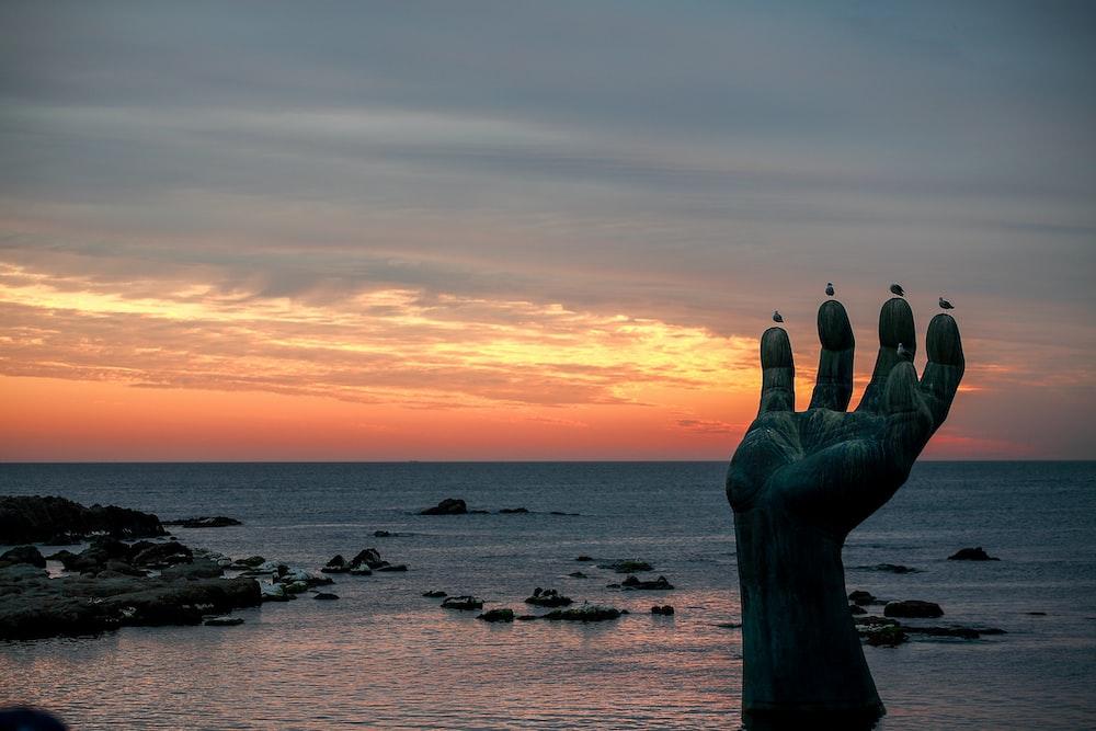 hand statue in seashore
