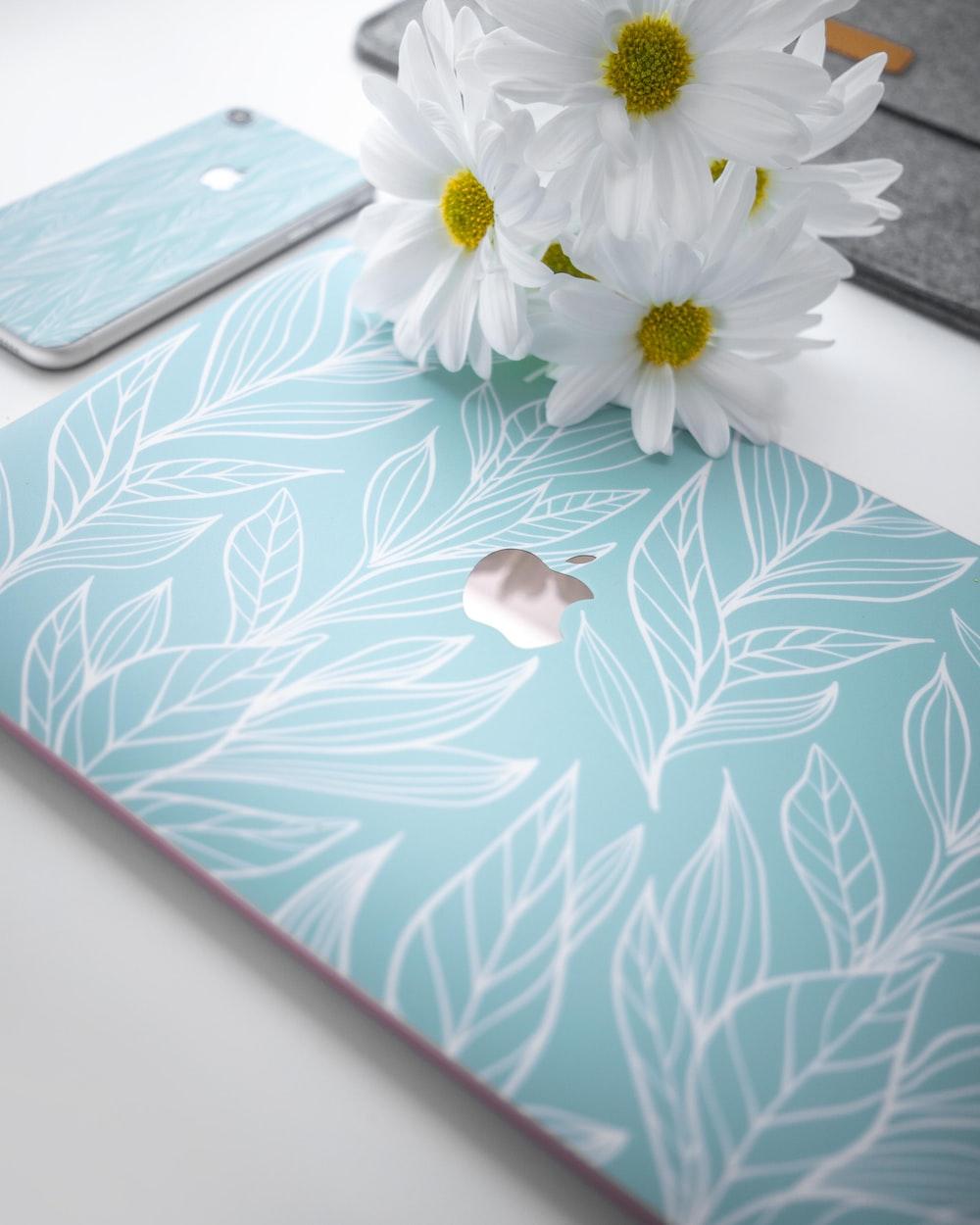 white daisies besides Apple laptop
