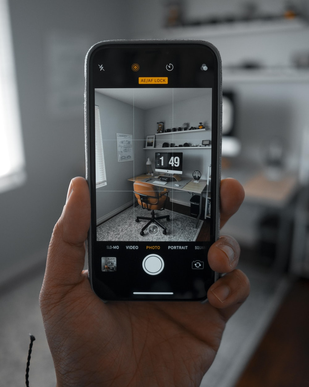 person using smartphone taking a picture of chair beside desk