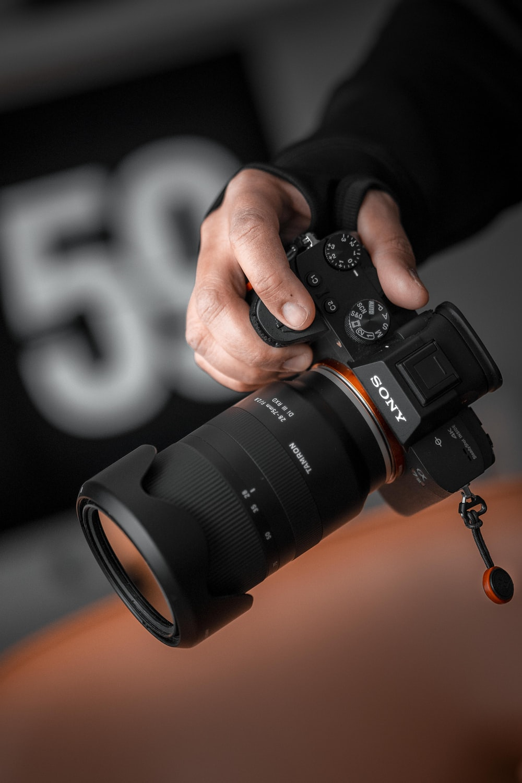 person holding black Sony DSLR camera