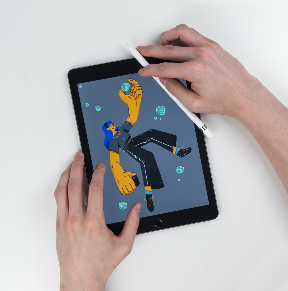 person holding Apple Pencil and space gray iPad