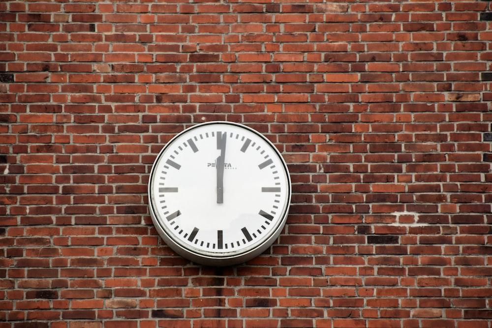 round white and black analog clock at 12;00