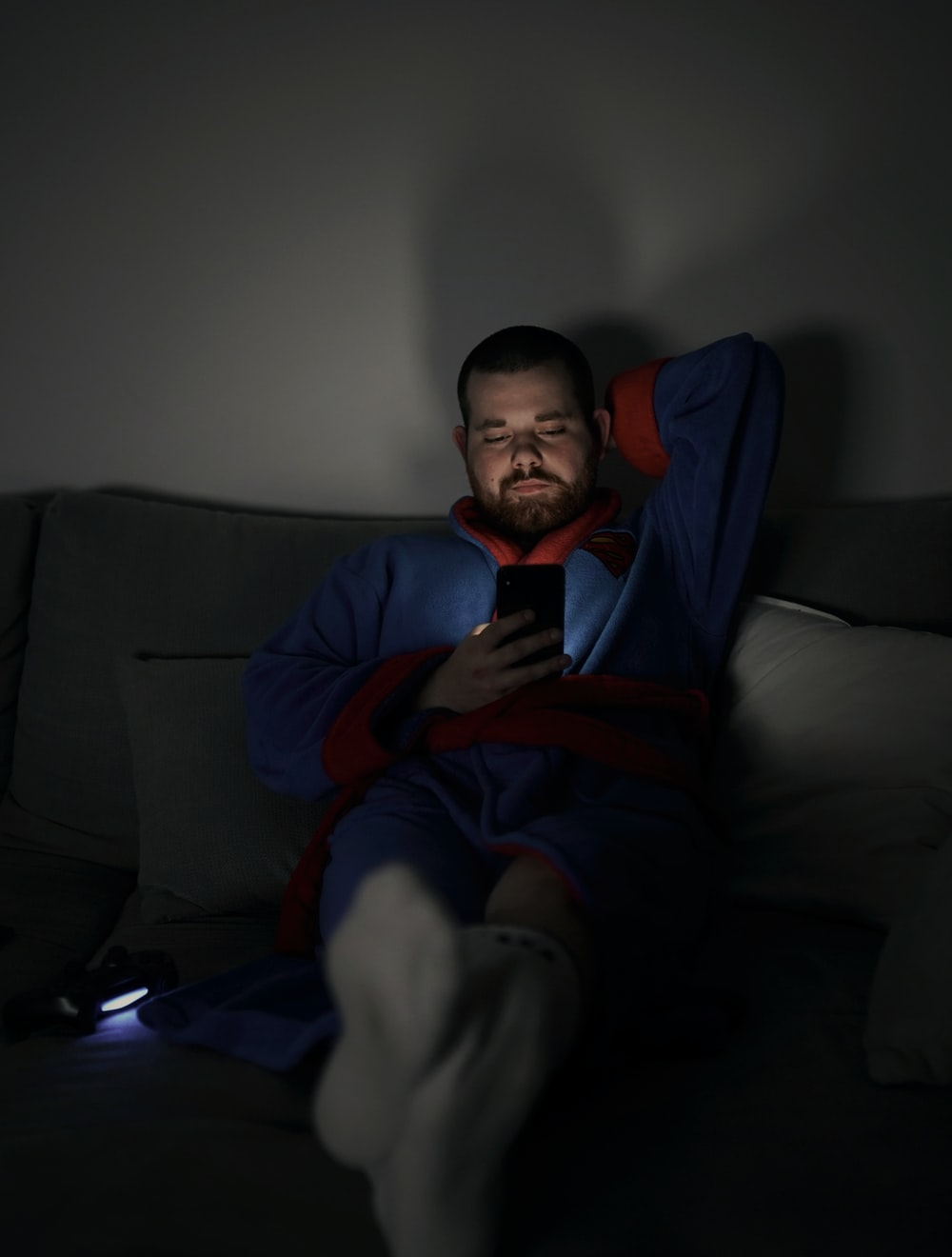 man sits on sofa while using smartphone