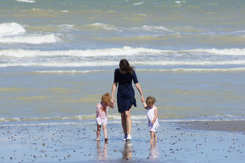 woman with 2 children walking on beach