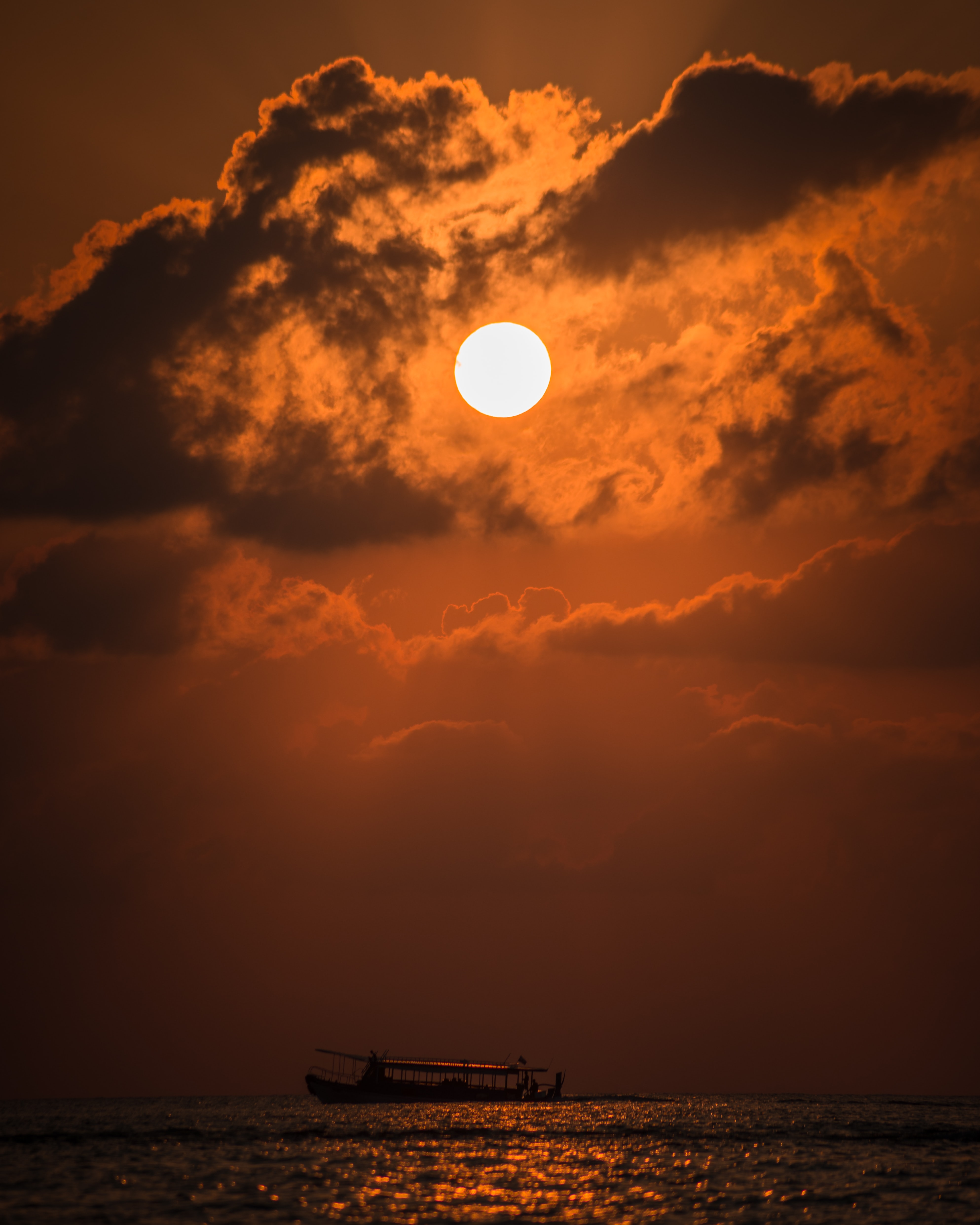 silhouette of boat under moon