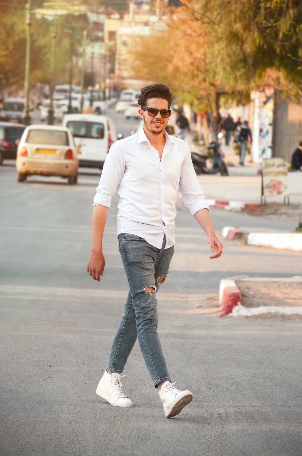 man wearing white dress shirt and distress blue jeans standing on road