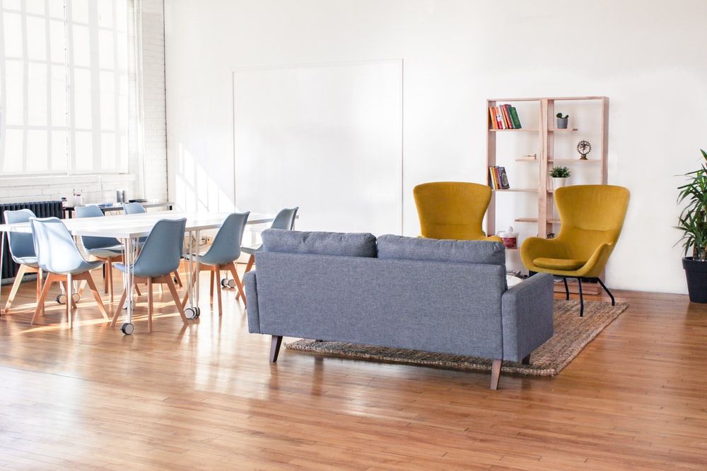 2-seat sofa in front of two armchairs near table with chairs