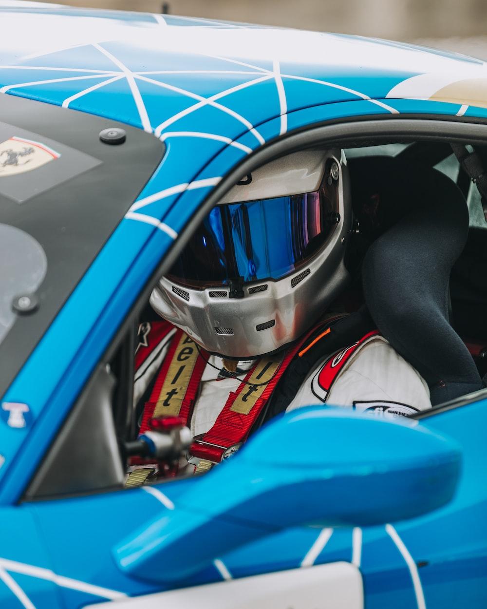 person in racing car wearing helmet