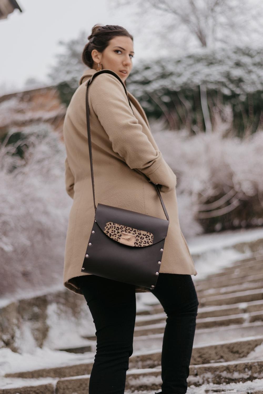 woman wearing brown coat walking near trees