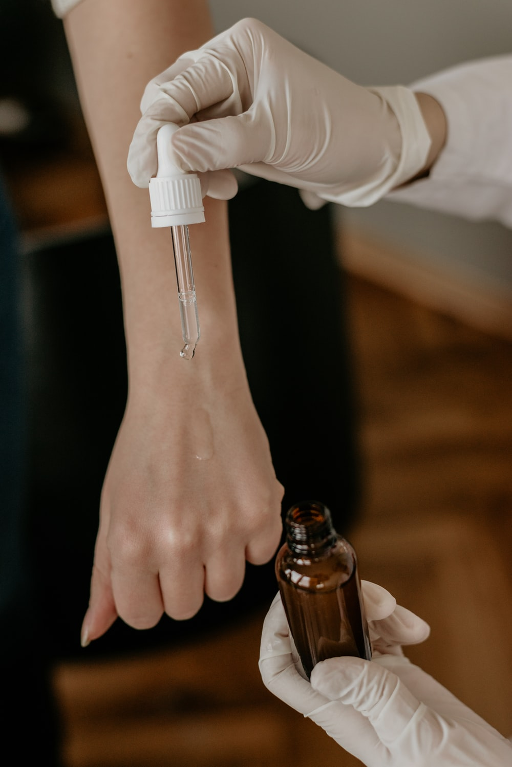 person with white gloves holding drop bottle pointing on another person's hand