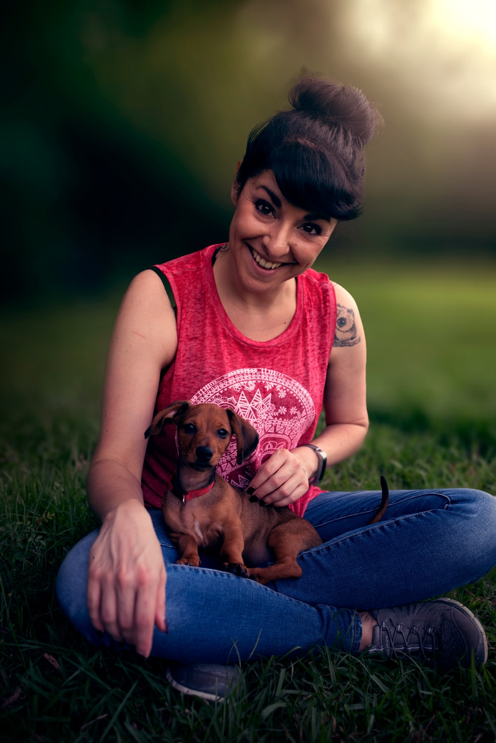 woman in pink sleeveless shirt holding brown puppy
