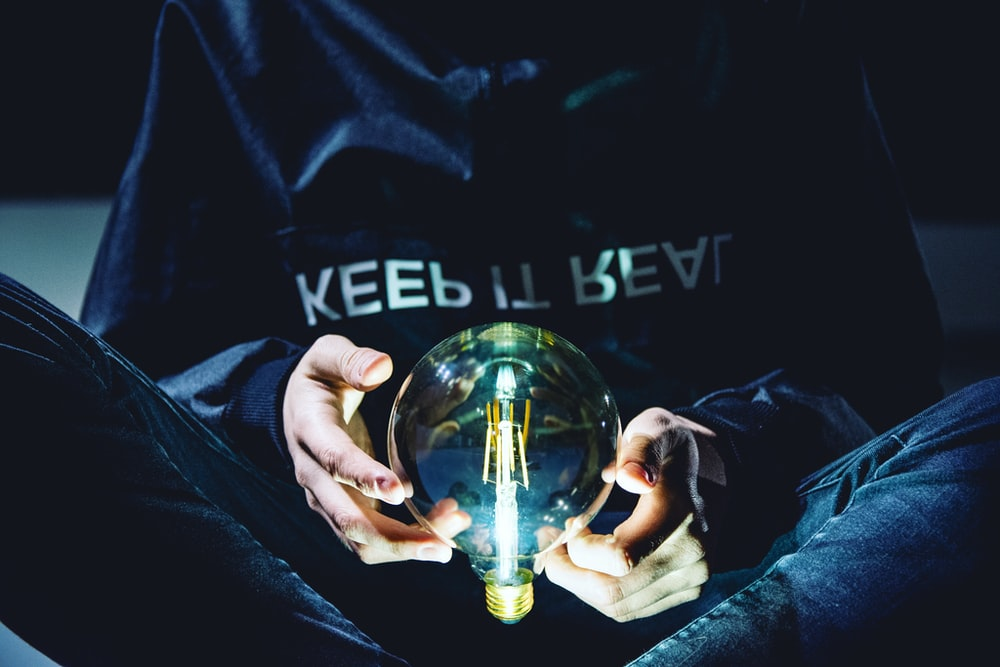 person holding clear glass light bulb