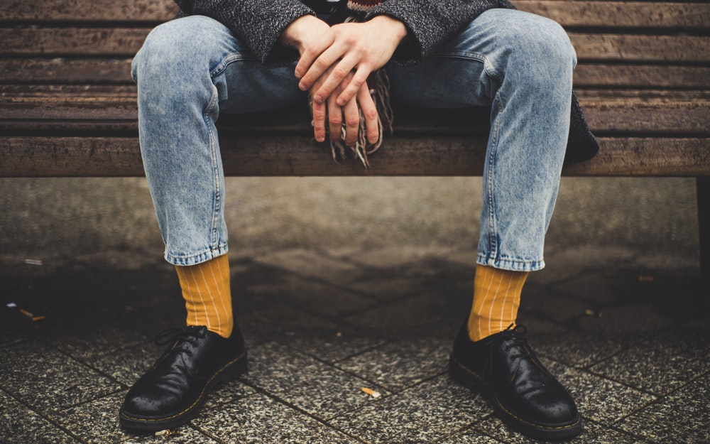 person in blue denim jeans sitting on brown bench