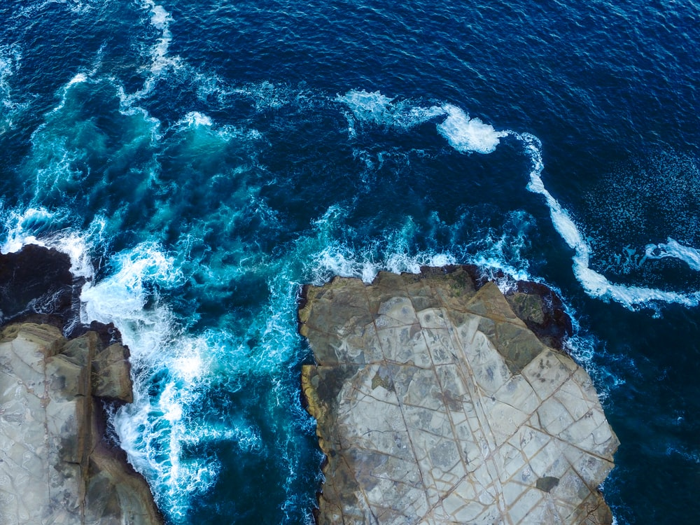 aerial photography of sea waves hitting coastal rocks during daytime