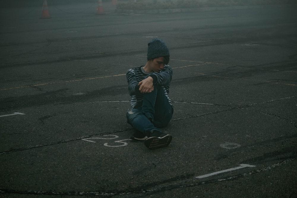 man sitting on roadway at daytime