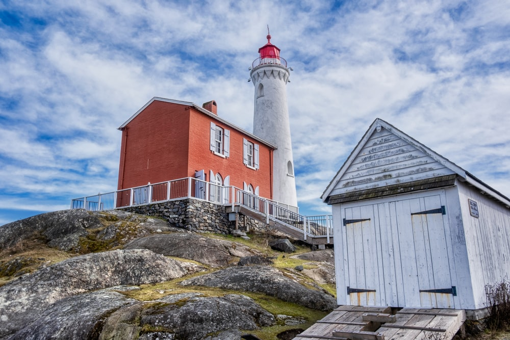 lighthouse beside brown barn