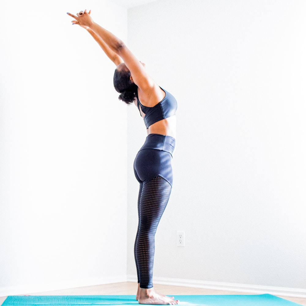 woman stretching wearing black bra and pants