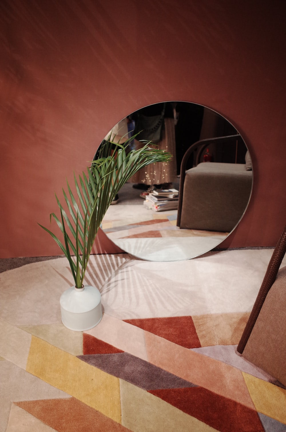 round mirror behind potted flower on floor inside room