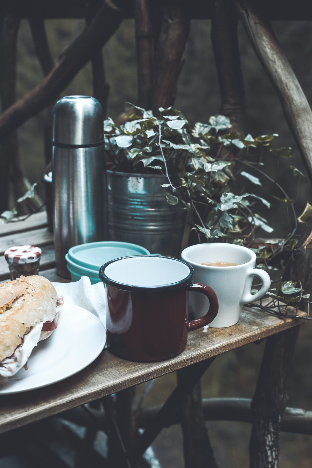 mugs beside plate with bread on table