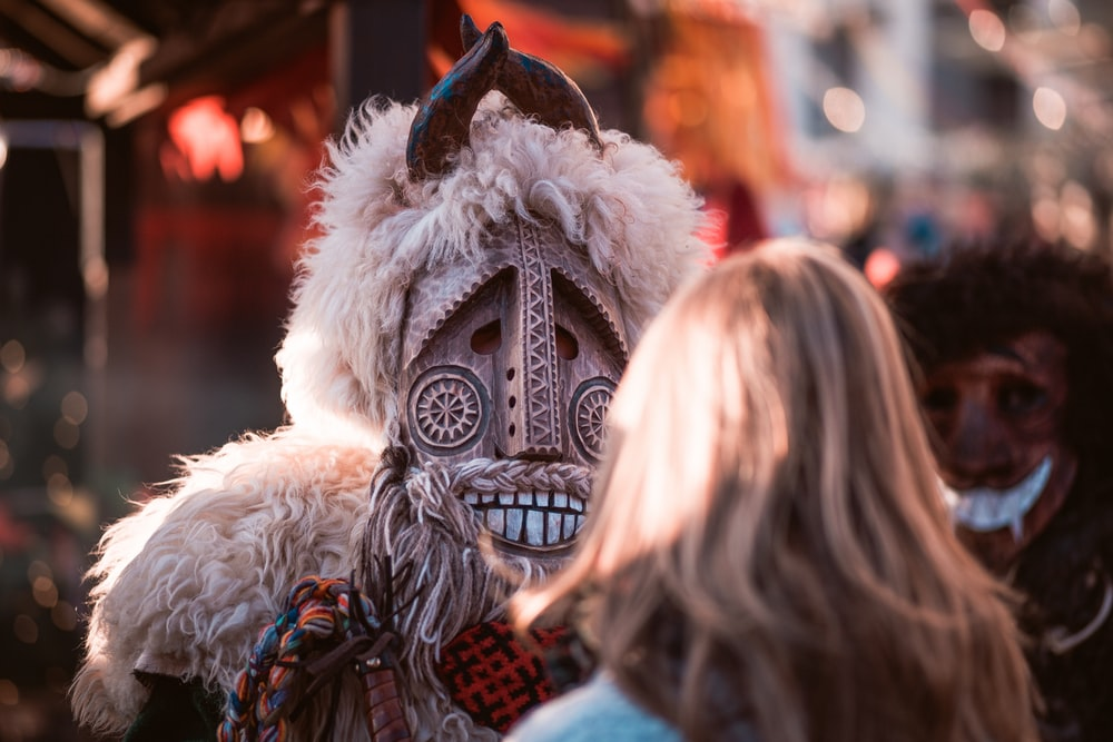 person wearing mask dancing in front of woman during daytime