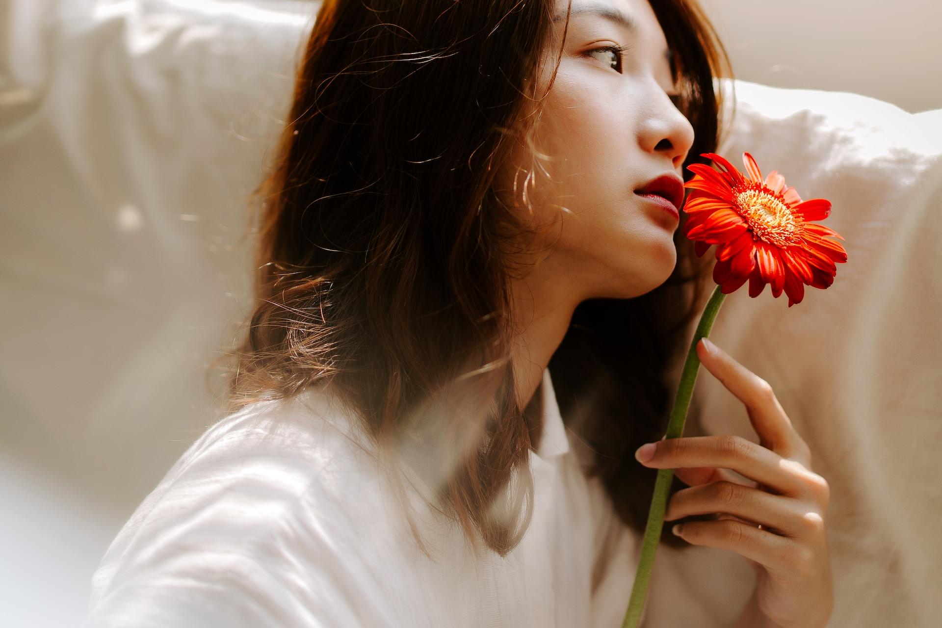 woman holding flower sitting on sofa