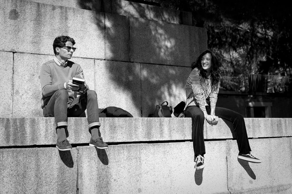 smiling woman looking on man sitting beside during daytime