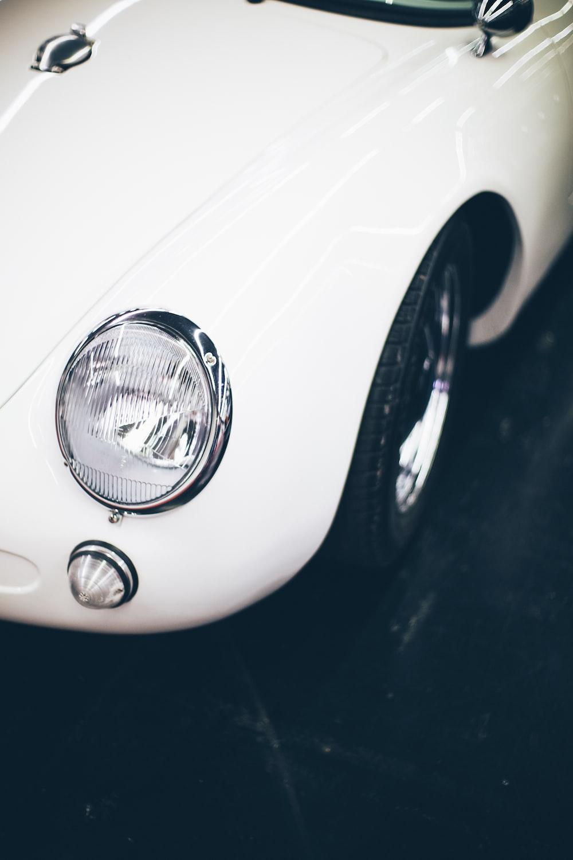 white vehicle parked on black pavement