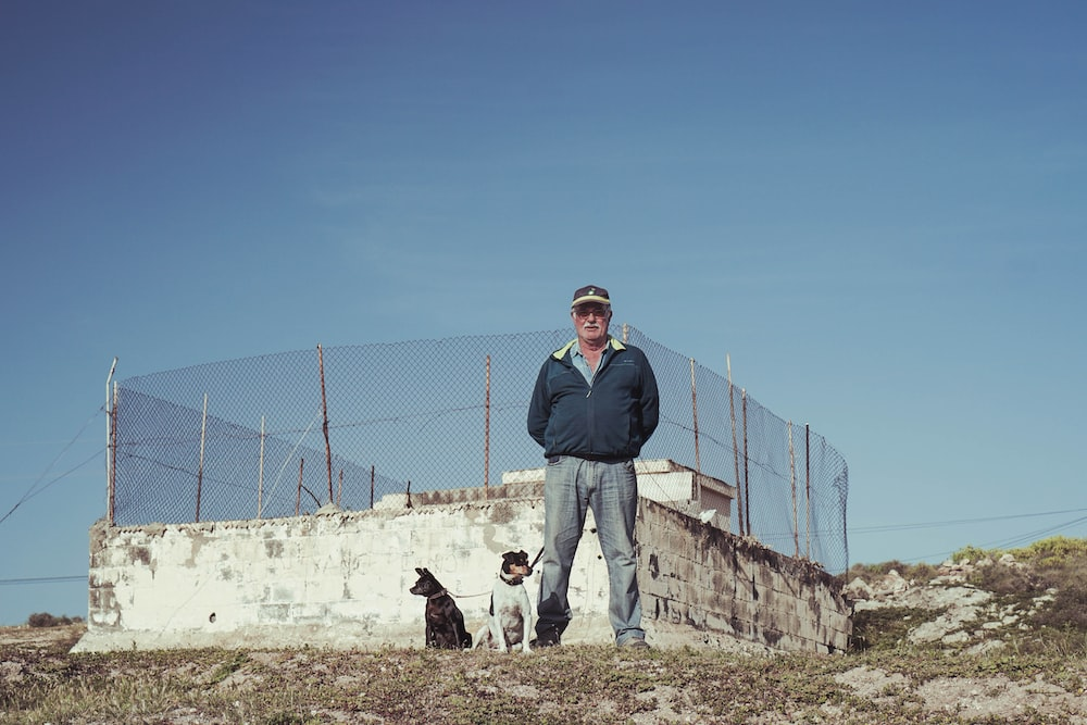 man standing beside dogs