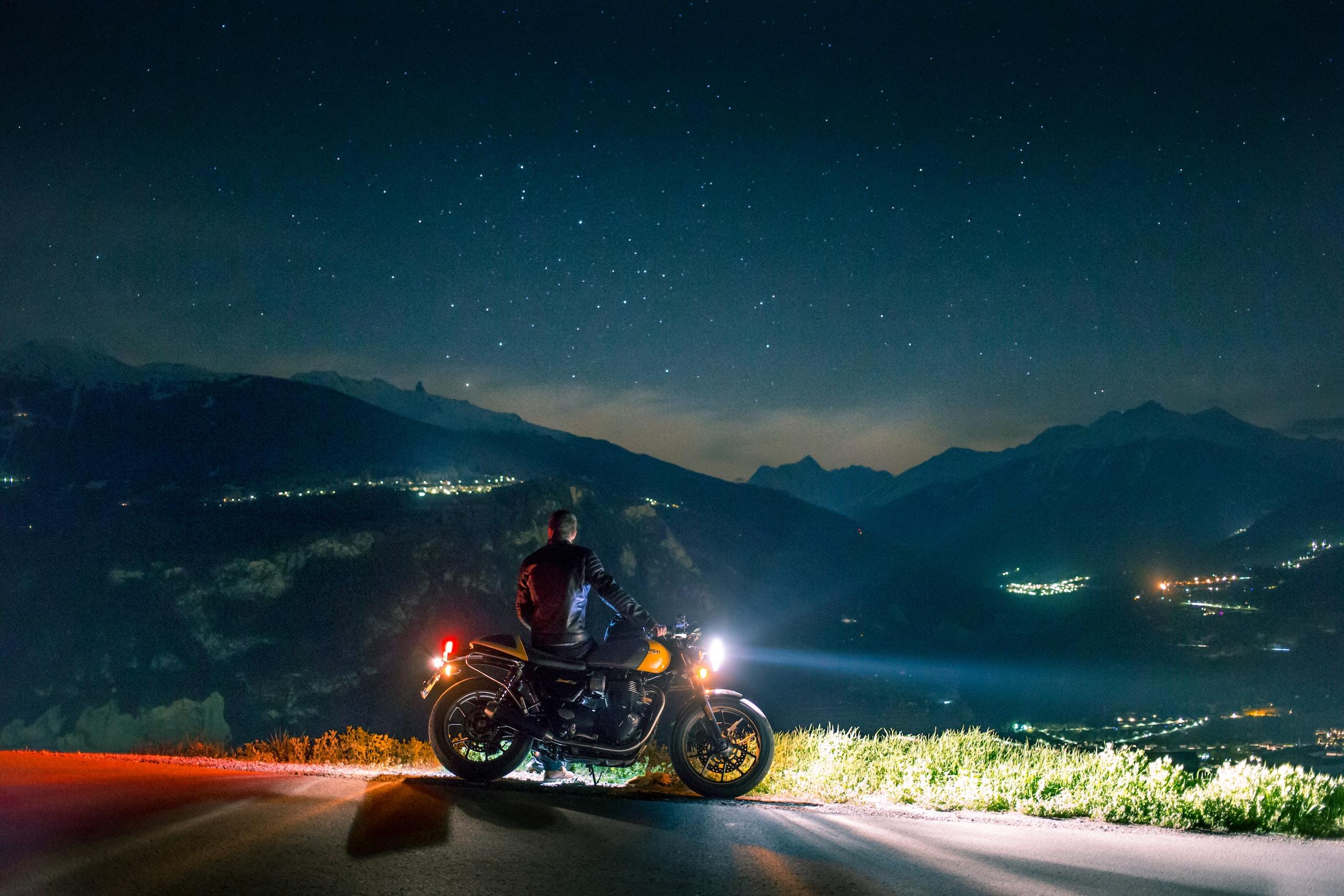man siting on motorcycle at night